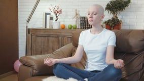 Η γυναίκα ασθενών με καρκίνο κάθεται σε έναν καναπέ και meditates απόθεμα βίντεο