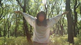 Η γυναίκα αυξάνει παραδίδει το ηλιόλουστο δάσος, κινηματογράφηση σε πρώτο πλάνο Χαμογελώντας χαλαρωμένο κορίτσι απόθεμα βίντεο