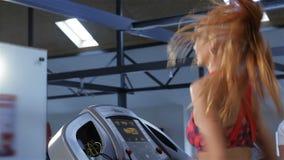 Η γυναίκα αυξάνει την ταχύτητα treadmill στο κέντρο ικανότητας απόθεμα βίντεο
