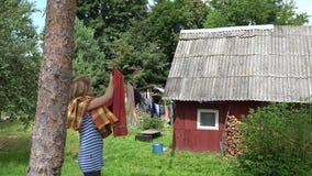 Η γυναίκα αφαιρεί το ξηρό περικάλυμμα πλυντηρίων από τη σκοινί για άπλωμα στη χώρα 4K φιλμ μικρού μήκους