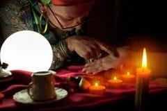 Η γυναίκα αφηγητών τύχης δείχνει το δάχτυλό της έναν άλλο φοίνικα γυναικών στοκ φωτογραφίες