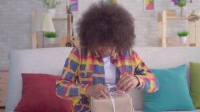 Η γυναίκα αφροαμερικάνων με ένα afro hairstyle ανοίγει τη συνεδρίαση δώρων στον καναπέ στο καθιστικό φιλμ μικρού μήκους