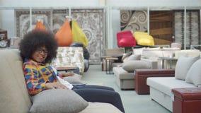 Η γυναίκα αφροαμερικάνων με ένα afro hairstyle επιλέγει έναν καναπέ σε ένα κατάστημα επίπλων φιλμ μικρού μήκους