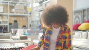 Η γυναίκα αφροαμερικάνων με ένα afro hairstyle επιλέγει έναν τάπητα σε ένα κατάστημα επίπλων απόθεμα βίντεο