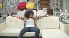 Η γυναίκα αφροαμερικάνων με ένα afro hairstyle επιλέγει τα έπιπλα superstore απόθεμα βίντεο