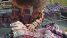Η γυναίκα αφροαμερικάνων με ένα afro hairstyle προσεκτικά επιλέγει έναν τάπητα στενό σε έναν επάνω καταστημάτων επίπλων απόθεμα βίντεο