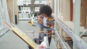 Η γυναίκα αφροαμερικάνων με ένα afro hairstyle το κατάστημα επιλέγει τα εργαλεία επισκευής απόθεμα βίντεο