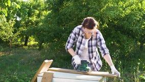 Η γυναίκα βάζει στα προστατευτικά γυαλιά και γυαλίζει την ξύλινη σανίδα με ηλεκτρικό sander φιλμ μικρού μήκους