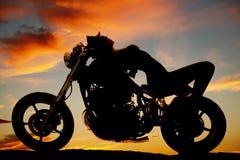 Η γυναίκα βάζει στο πίσω μέρος της σκιαγραφίας μοτοσικλετών Στοκ Εικόνες