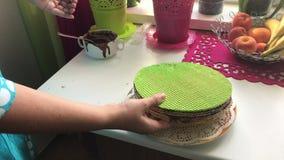 Η γυναίκα βάζει τα κέικ γκοφρετών, που λερώνονται με τη σοκολάτα σε έναν σωρό απόθεμα βίντεο