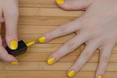 Η γυναίκα βάζει την κίτρινη στιλβωτική ουσία καρφιών Στοκ Εικόνες
