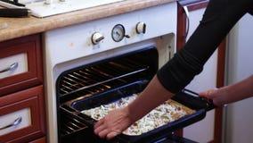 Η γυναίκα βάζει την πίτσα στο φούρνο απόθεμα βίντεο