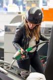 Η γυναίκα βάζει τη βενζίνη μέσα σε ένα μηχανικό δίκυκλο στοκ φωτογραφία