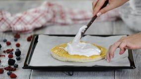 Η γυναίκα βάζει τη μαρέγκα στην ψημένη ζύμη ριπών Κατασκευή του βαλμένου σε στρώσεις κέικ με τα θερινά μούρα φιλμ μικρού μήκους