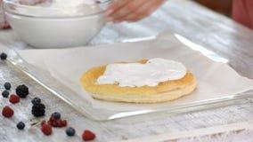 Η γυναίκα βάζει τη μαρέγκα στην ψημένη ζύμη ριπών Κατασκευή του βαλμένου σε στρώσεις κέικ με τα θερινά μούρα απόθεμα βίντεο