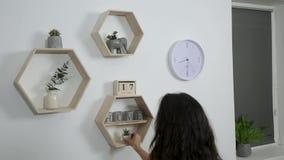 Η γυναίκα βάζει το ντεκόρ και ανθίζει στα ράφια στον τοίχο απόθεμα βίντεο
