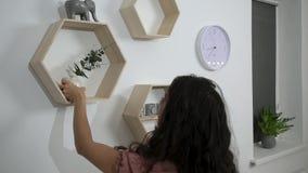 Η γυναίκα βάζει το ντεκόρ και ανθίζει στα ράφια στον τοίχο φιλμ μικρού μήκους