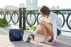 Η γυναίκα βγάζει τα παπούτσια της Ποταμός υποβάθρου, αστικό ύφος στοκ φωτογραφία