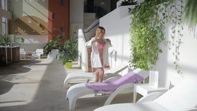 Η γυναίκα βγάζει την τήβεννο και ξαπλώνει στο μόνιππο longue με μια πετσέτα στη SPA απόθεμα βίντεο