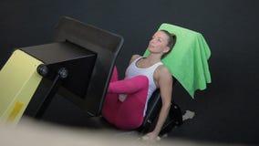 Η γυναίκα βρίσκεται στον πάγκο κλίσεων και πιέζει τη μηχανή από την που οδηγείται στη γυμναστική απόθεμα βίντεο