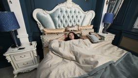 Η γυναίκα βρίσκεται στο κρεβάτι απόθεμα βίντεο