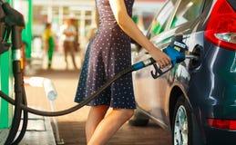 Η γυναίκα γεμίζει τη βενζίνη στο αυτοκίνητό της στοκ φωτογραφία