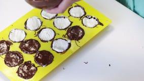 Η γυναίκα γεμίζει τη μάζα στάρπης με μια μορφή που λερώνεται με τη λειωμένη σοκολάτα Δίπλα στον πίνακα είναι συστατικά για το μαγ απόθεμα βίντεο