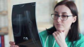 Η γυναίκα γιατρών εξετάζει το των ακτίνων X αργό MO εικόνων απόθεμα βίντεο