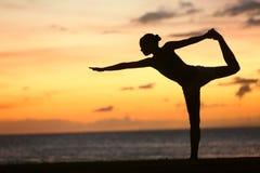 Η γυναίκα γιόγκας στο γαλήνιο ηλιοβασίλεμα να κάνει παραλιών θέτει