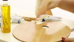 Η γυναίκα γονιμοποιεί μια παλέτα για τα ελαιοχρώματα Ο καλλιτέχνης προετοιμάζει easel για το σχέδιο Όμορφο πετρέλαιο για τη διαπό φιλμ μικρού μήκους
