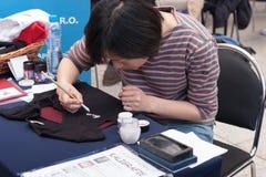 Η γυναίκα γράφει την ιαπωνική καλλιγραφία σε Animefest Στοκ εικόνες με δικαίωμα ελεύθερης χρήσης