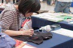 Η γυναίκα γράφει την ιαπωνική καλλιγραφία σε Animefest Στοκ φωτογραφία με δικαίωμα ελεύθερης χρήσης