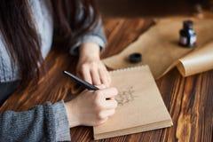 Η γυναίκα γράφει την καλλιγραφική γραφή σε χαρτί τεχνών με τη μάνδρα μελανιού στοκ εικόνες