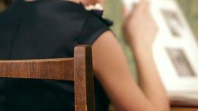 Η γυναίκα γυρίζει τις σελίδες ενός λευκώματος απόθεμα βίντεο