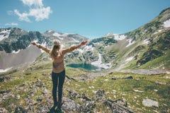 Η γυναίκα δίνει αυξημένος απολαμβάνοντας την περιπέτεια τρόπου ζωής ταξιδιού βουνών και λιμνών τοπίων στοκ εικόνα