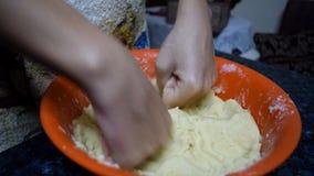 Η γυναίκα δίνει κοντά επάνω να ζυμώσει τη ζύμη σε αργή κίνηση φιλμ μικρού μήκους