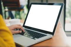 Η γυναίκα δίνει το φορητό προσωπικό υπολογιστή δακτυλογράφησης με την κενή οθόνη στον πίνακα στη καφετερία Κενή χλεύη οθόνης lap- στοκ εικόνα