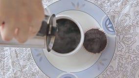 Η γυναίκα δίνει το χύνοντας καφέ στο φλυτζάνι απόθεμα βίντεο