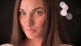 Η γυναίκα δαγκώνει τα χείλια της και προσελκύει τη κάμερα στο smth στο υπόβαθρο blured-φω'των φιλμ μικρού μήκους
