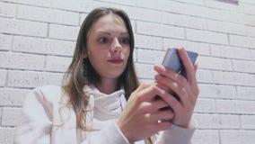 Η γυναίκα δακτυλογραφεί ένα μήνυμα στην κινητές τηλεφωνικές συνεδρίαση και την αναμονή κάποιος στον καφέ φιλμ μικρού μήκους