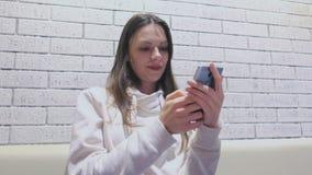 Η γυναίκα δακτυλογραφεί ένα μήνυμα στην κινητές τηλεφωνικές συνεδρίαση και την αναμονή κάποιος στον καφέ απόθεμα βίντεο