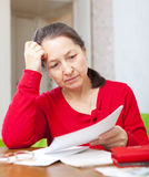 Η γυναίκα διαβάζει τις πληρωμές στο σπίτι στοκ φωτογραφίες