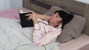 Η γυναίκα διαβάζει το βιβλίο πριν από τον ύπνο απόθεμα βίντεο