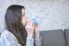 Η γυναίκα διογκώνει μια μεγάλη φυσαλίδα από μπλε slime Παιχνίδι με slime στοκ εικόνες