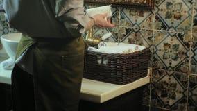Η γυναίκα διπλώνει τις καθαρές μαλακές πετσέτες στο καλάθι, που καθαρίζει την έννοια απόθεμα βίντεο