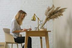 Η γυναίκα είναι γραφή στον πίνακα στοκ εικόνες