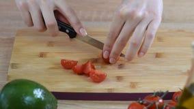 Η γυναίκα είναι τέμνουσες ντομάτες κερασιών για τη σαλάτα στον ξύλινο πίνακα απόθεμα βίντεο