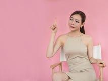 Η γυναίκα δείχνει το δάχτυλό της επάνω και κάθεται στην καρέκλα στοκ εικόνες