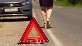 Η γυναίκα εγκατέστησε το κόκκινο τρίγωνο - σημάδι στάσεων έκτακτης ανάγκης φιλμ μικρού μήκους