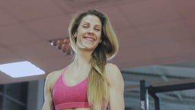 Η γυναίκα εκπαιδεύει με έναν φραγμό στη γυμναστική beautiful body απόθεμα βίντεο